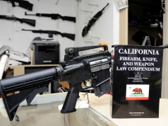 A 736-page California gun law book is on display along with guns at Aegis Trading Enterprises gun shop in Burbank California