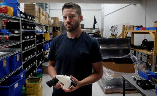Cody Wilson poses with an example of a 3-D printed gun at his factory in Austin