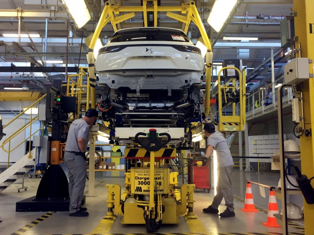 Assembly workers fix the chassis of a DS7 Crossback plug-in hybrid SUV to its body, inside the prototypes workshop at PSA Groups Sochaux plant