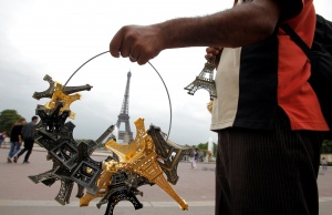 A souvenir vendor sells Eiffel tower models for tourists in front the Eiffel Tower at the Trocadero in Paris
