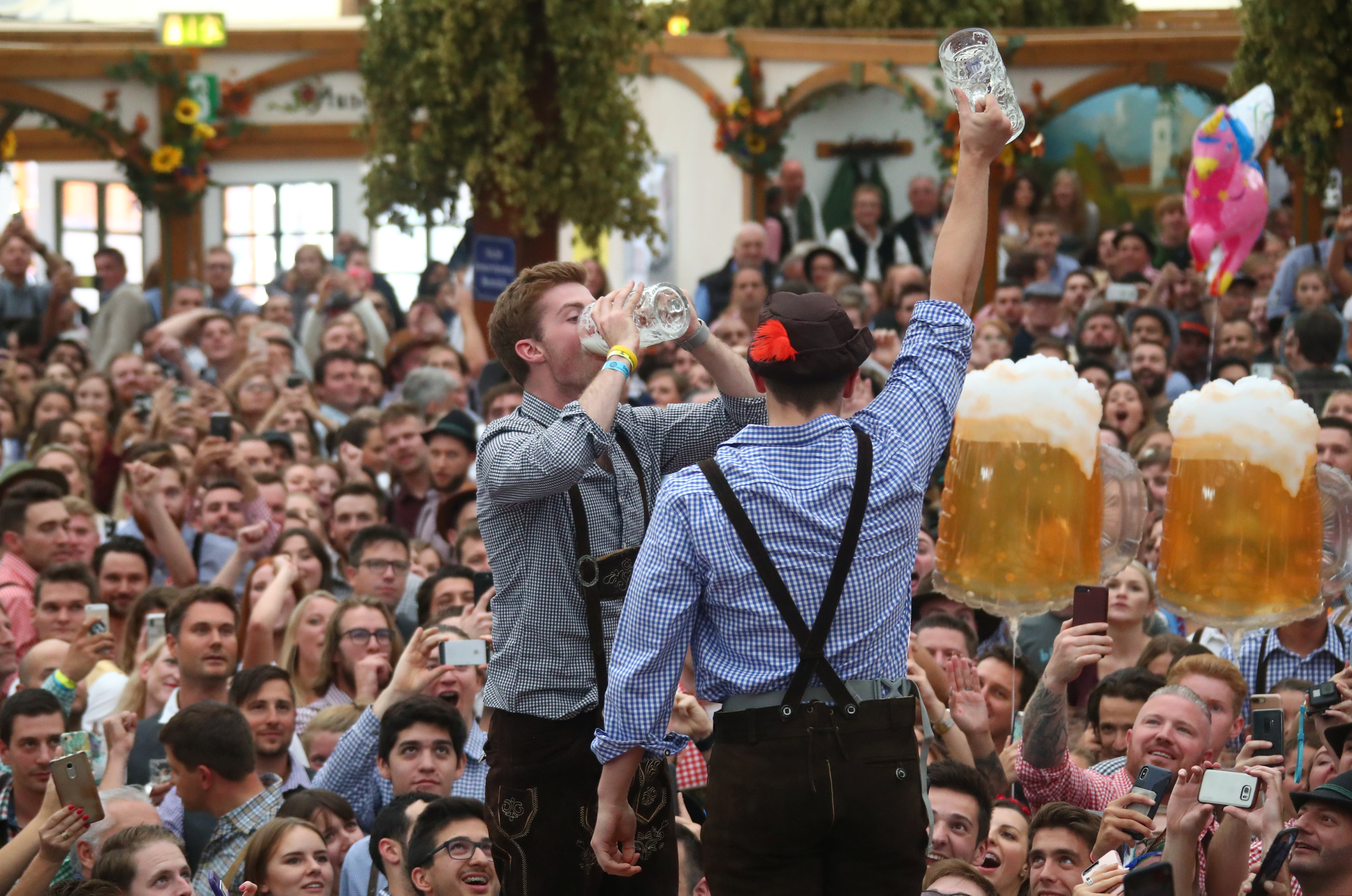 A visitor drinks beer during the opening day of the 185th Oktoberfest in Munich