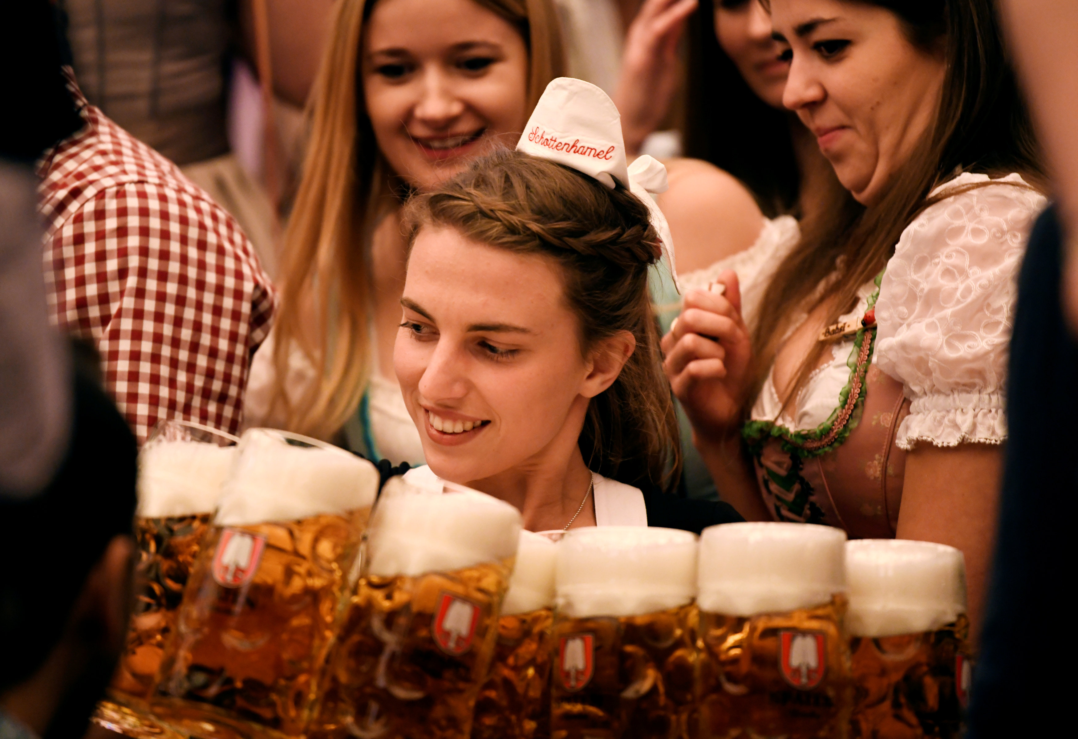 A waitress carries mugs of beer during the opening day of the 185th Oktoberfest in Munich
