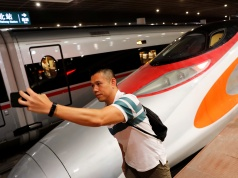 A passenger poses next to the first train that departed from Hong Kong during the first day of service of the Hong Kong Section of the Guangzhou-Shenzhen-Hong Kong Express Rail Link, in Shenzhen