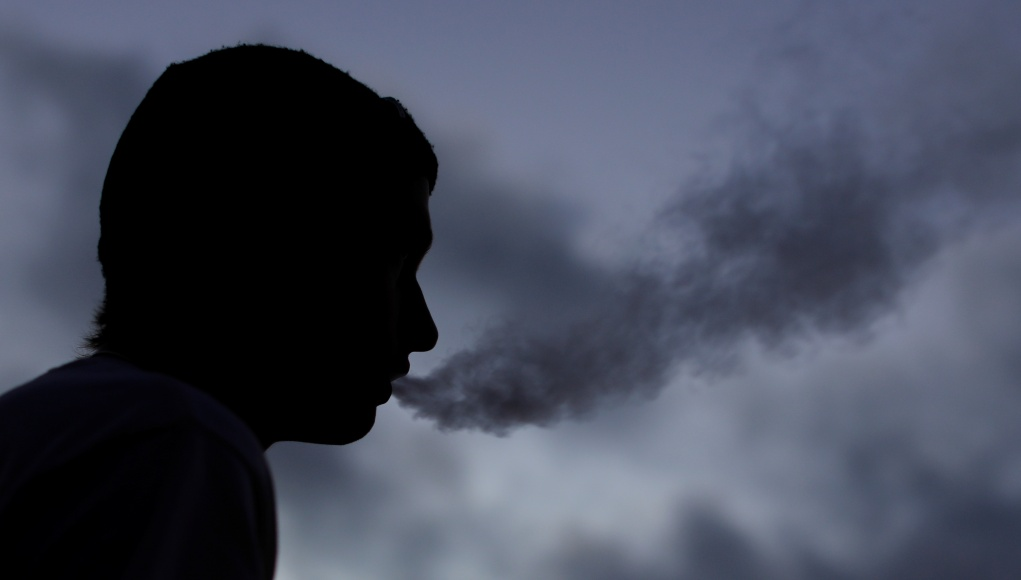 A young man smokes a Suorin Drop electronic cigarette in this picture illustration