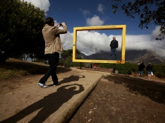 Visitors pose for pictures against Table Mountain at a viewing site in Cape Town
