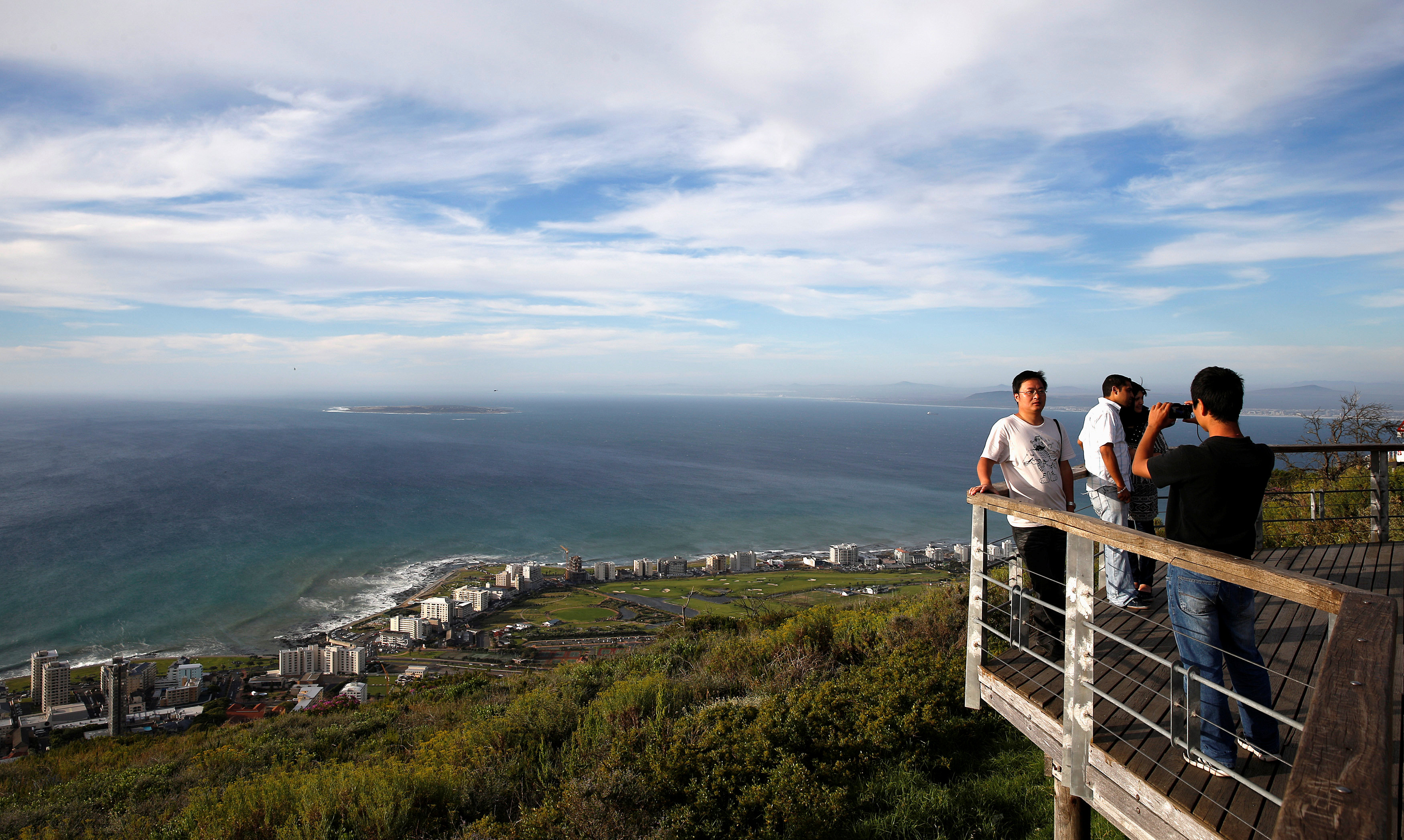 Tourists take pictures from a viewing platform in Cape Town, South Africa
