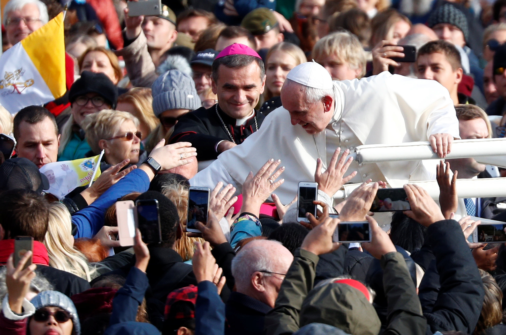 Pope Francis greets people as he arrives to l