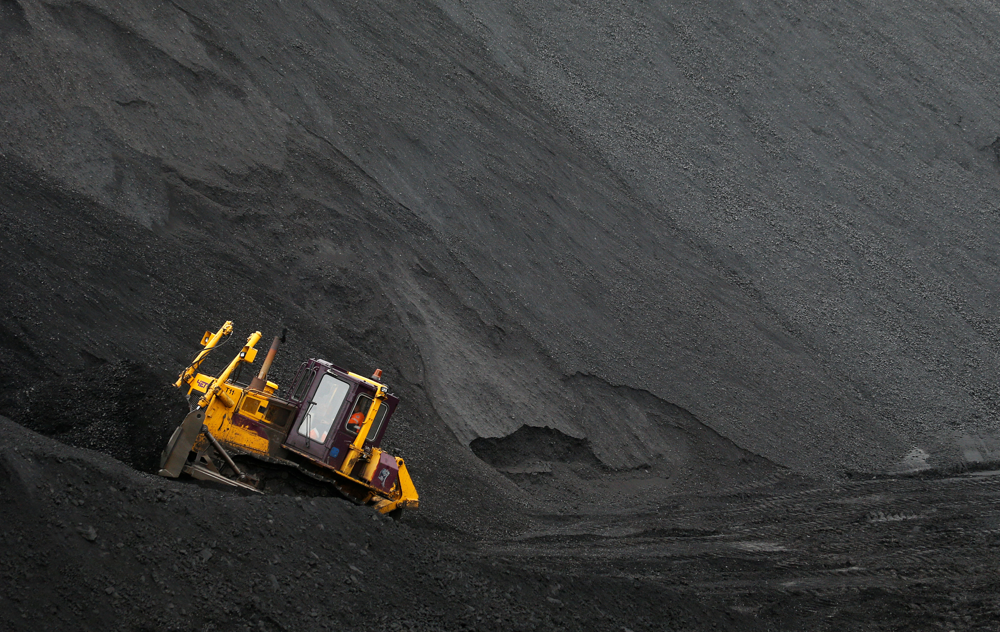 A labourer operates a bulldozer on a stockpile of coal at Vorgashorskaya mine outside the far northern city of Vorkuta