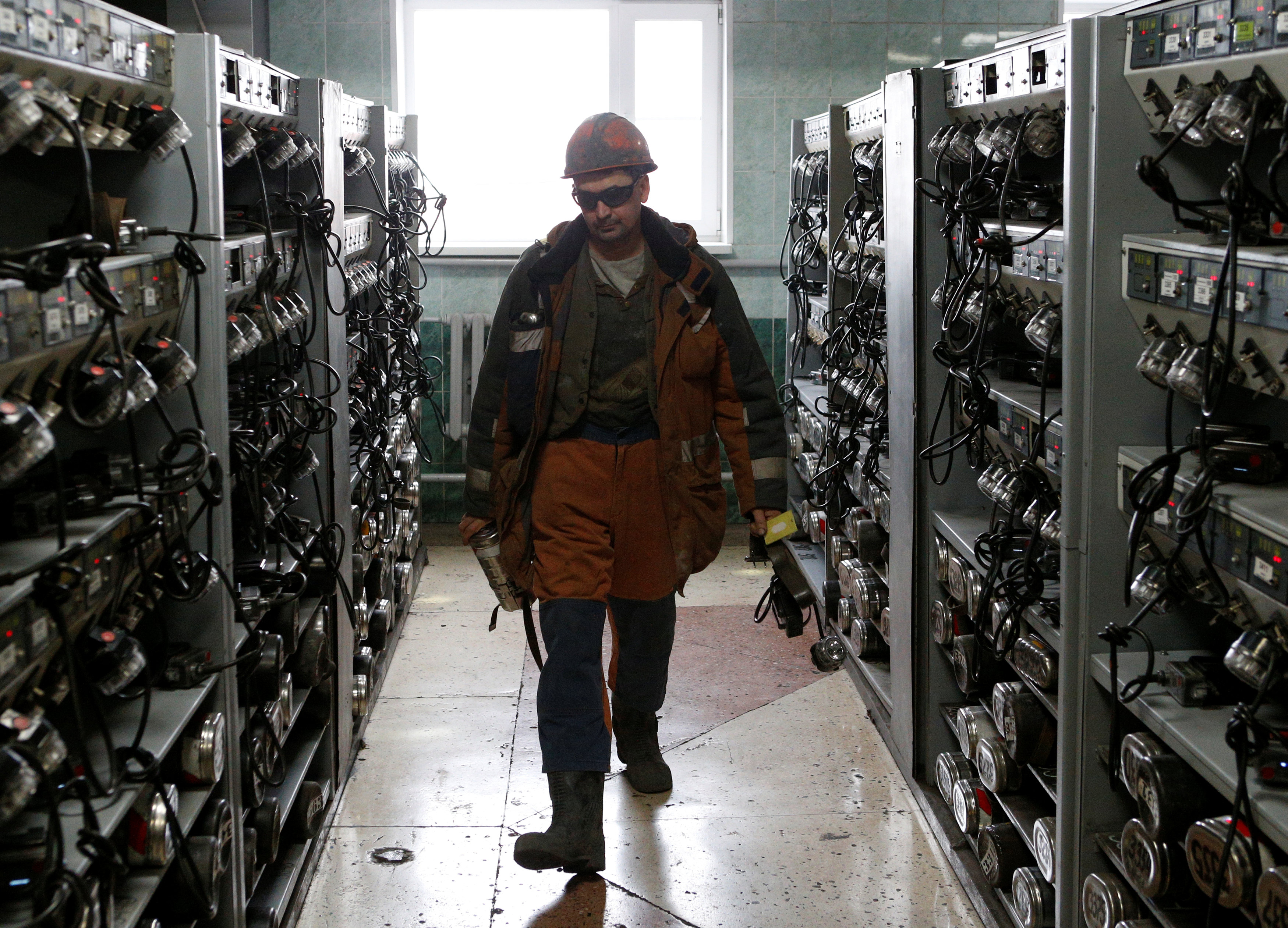 A miner walks past shelves with equipment before descending into the Vorgashorskaya mine near the far northern city of Vorkuta