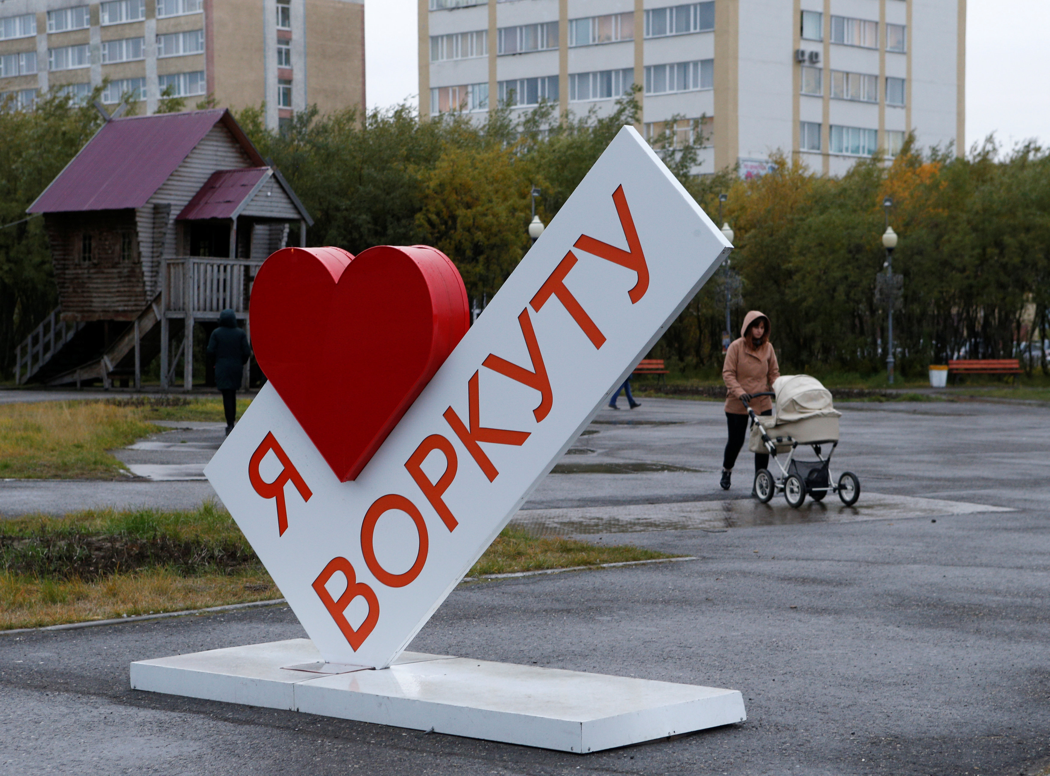 "A woman pushes a pram as she walks past an installation, which reads ""I love Vorkuta"" in the far northern city of Vorkuta"