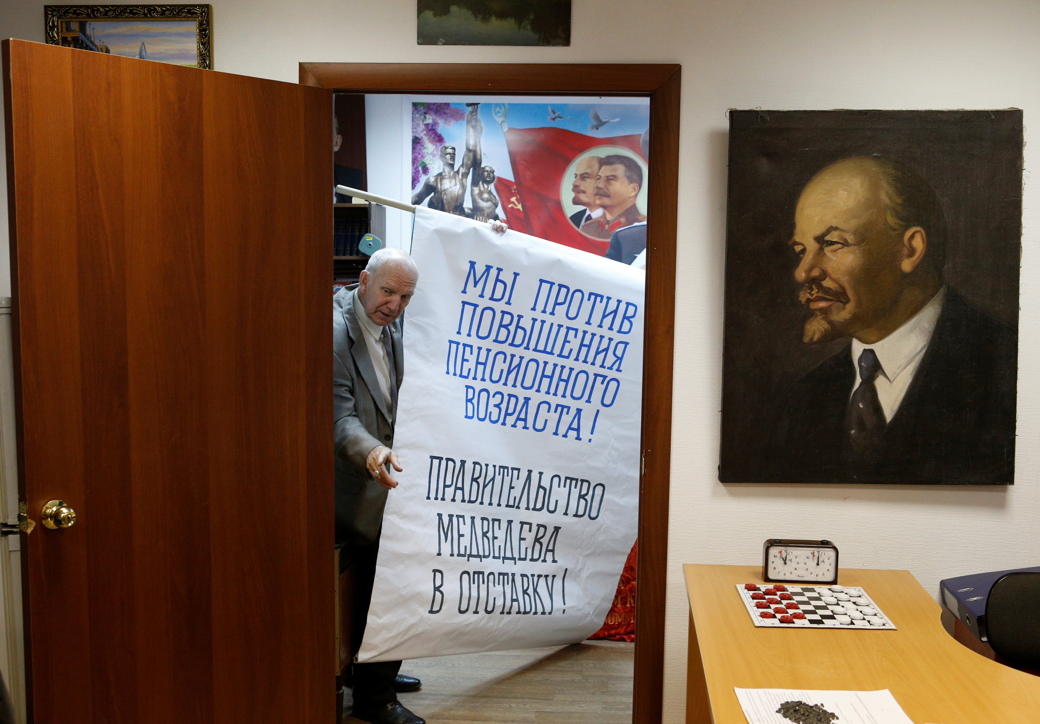 Vladimir Sorokin, head of the Communist Party local branch, carries a placard during an interview in his office in the far northern city of Vorkuta