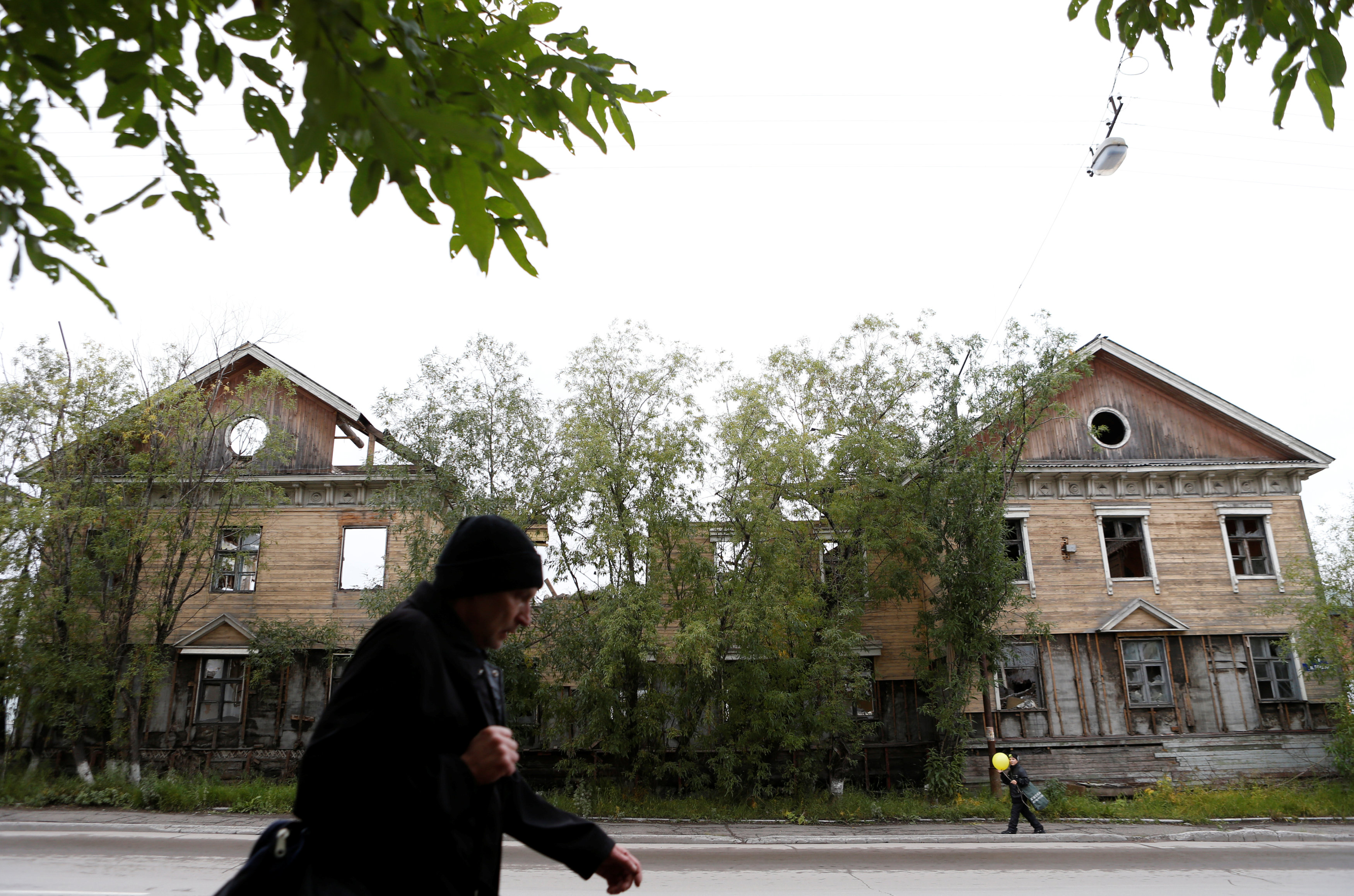Pedestrians walk past an abandoned building in the far northern city of Vorkuta