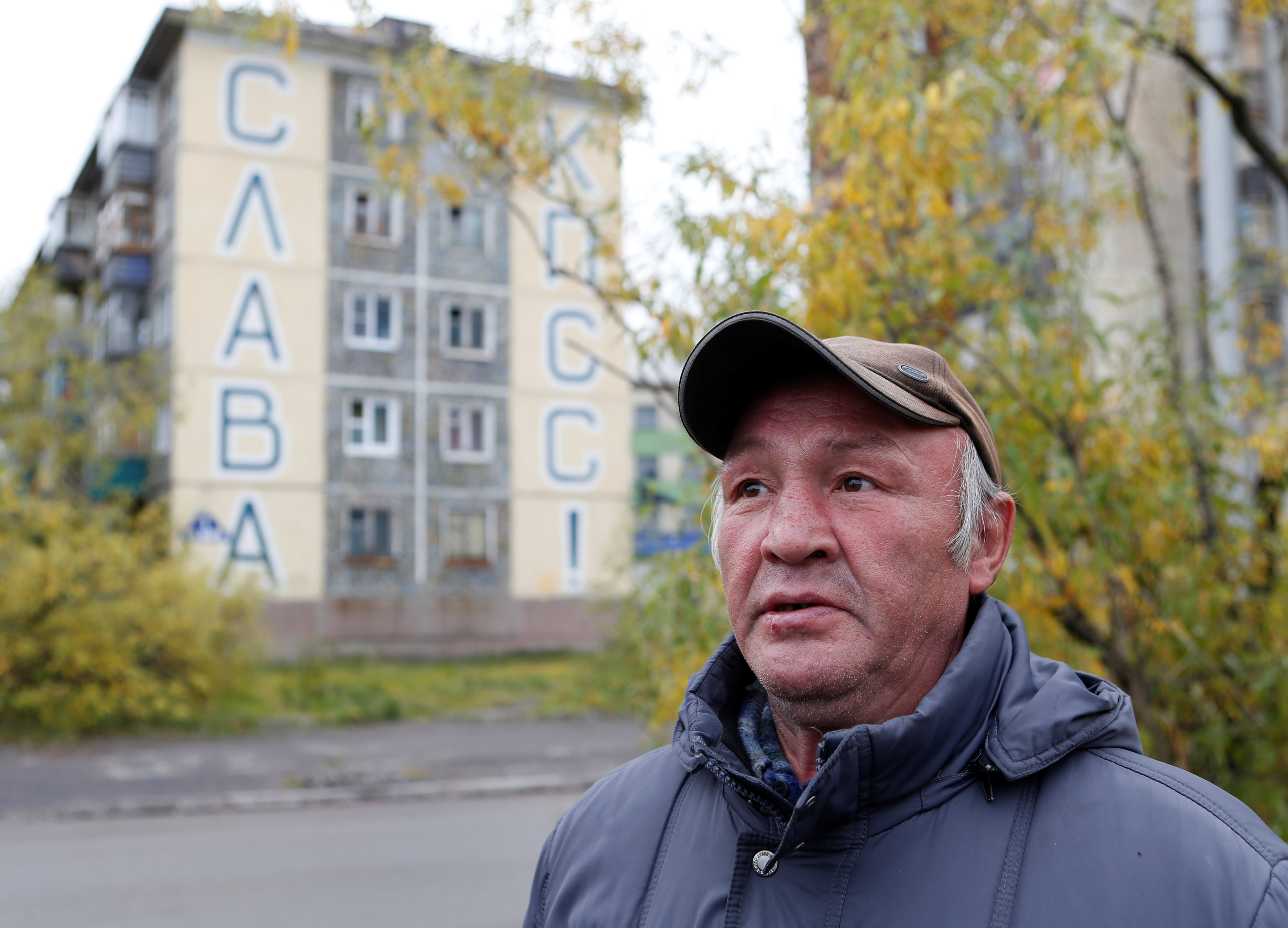 "A local resident is seen in front of a building, with a sign reads ""Glory to the Communist Party of the Soviet Union (CPSU)!"" seen on its facade, in a street in the far northern city of Vorkuta"