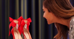 A visitor takes a look at the Red Ruby and Diamond pair of shoes worth $27000 USD displayed at the Burj Al Arab Hotel in Dubai