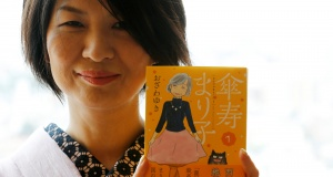 Yuki Ozawa, the comic book author of ÒSanju Mariko,Ó poses with her comic book during an interview with Reuters in Tokyo