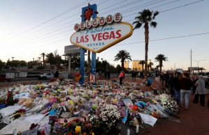 "The ""Welcome to Las Vegas"" sign is surrounded by flowers and items, left after the October 1 mass shooting, in Las Vegas"