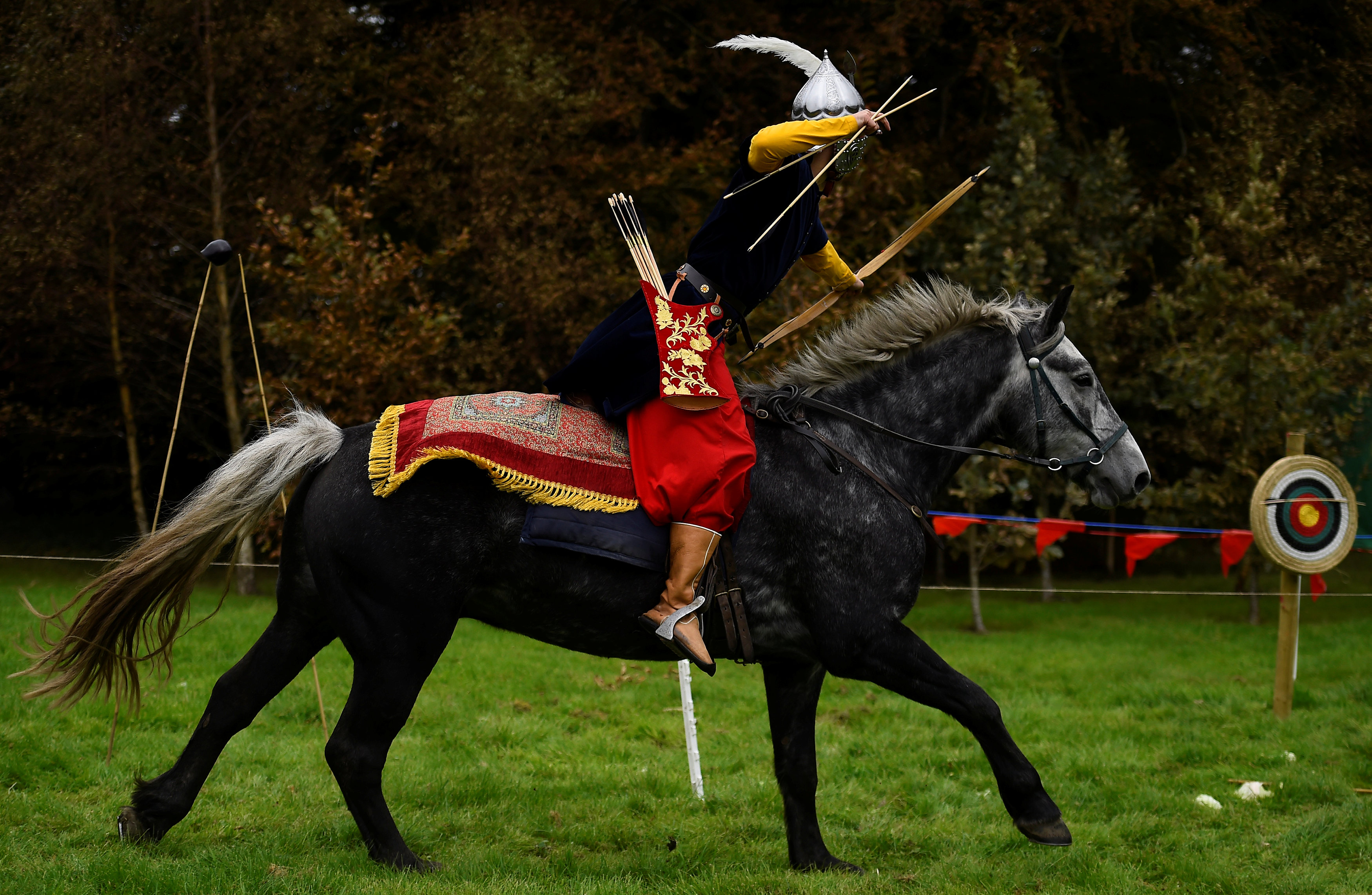 Gokmen Altinkulp dressed as an Ottoman warrior rides horse Bento to demonstrate horseback archery skills during a medieval combat festival at Claregalway castle in Galway