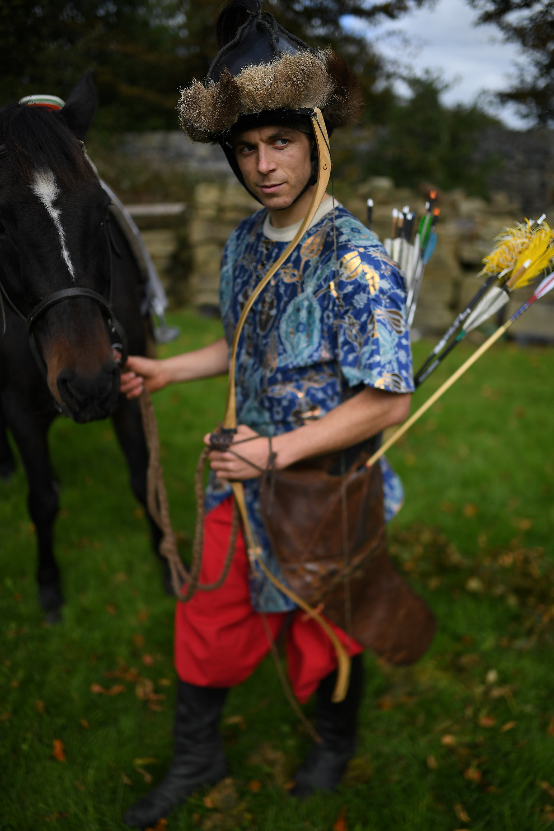 Andrew O'Donnghaile dressed as an Ottoman warrior prepares to mount horse Bilbo to demonstrate horseback archery skills during a medieval combat festival at Claregalway castle in Galway