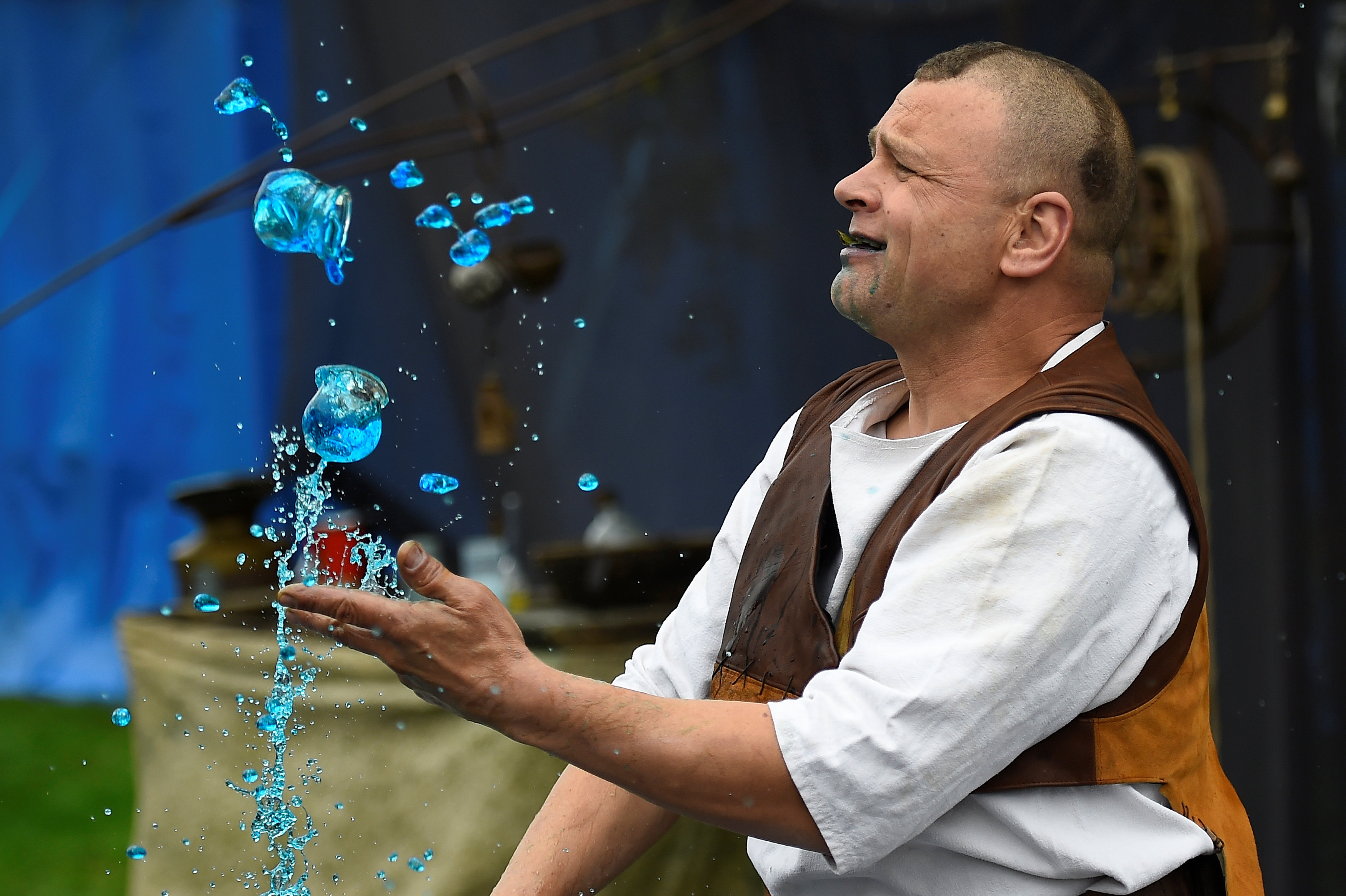 A man dressed as an alchemist demonstrates chemical tricks with bottles of liquids during a medieval combat festival at Claregalway castle in Galway