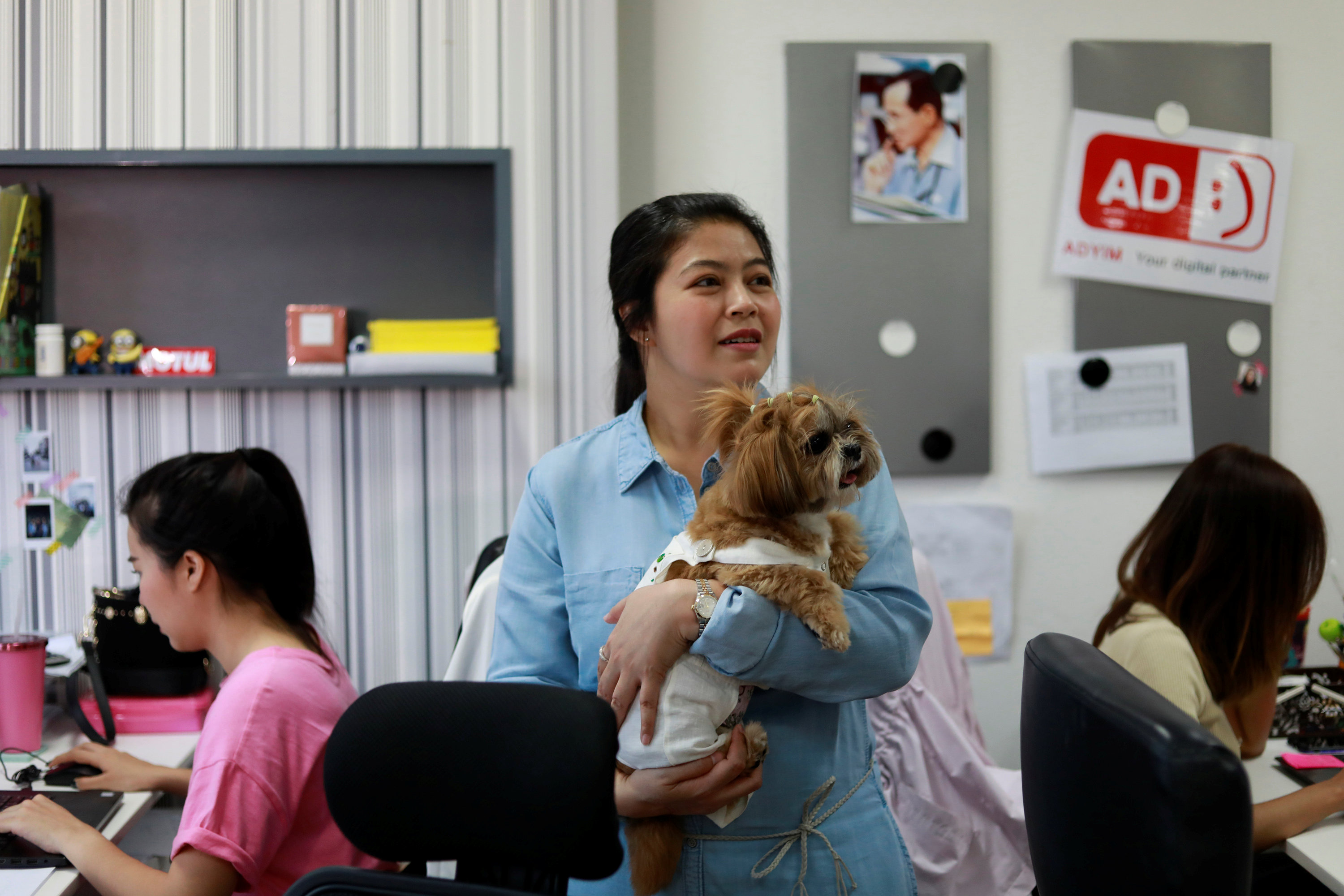 irmas holds a dog as she works in an office of a digital advertising agency which promotes bring-your-dog-to-work in Bangkok
