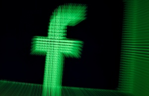A 3D-printed Facebook logo is seen in front of displayed binary digits in this illustration