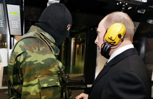 Russian President Putin and a masked security officer stand at a shooting gallery in Moscow