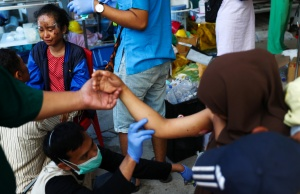 Victims of the earthquake and tsunami receive medical treatment inside a hospital in Palu