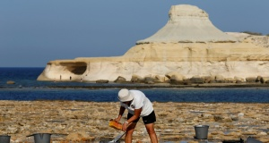 Josephine Xuereb scoops salt into buckets at the salt pans at Xwejni, outside the village of Zebbug on the island of Gozo