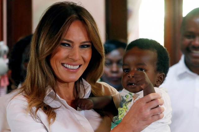U.S. First Lady Melania Trump holds a child at The Nest Children's Home in Nairobi