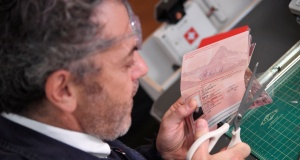 Artist Tom Sachs is seen producing a Swiss 'passport' as part of his installation 'Swiss Passport Office' at the Frieze At Fair in London
