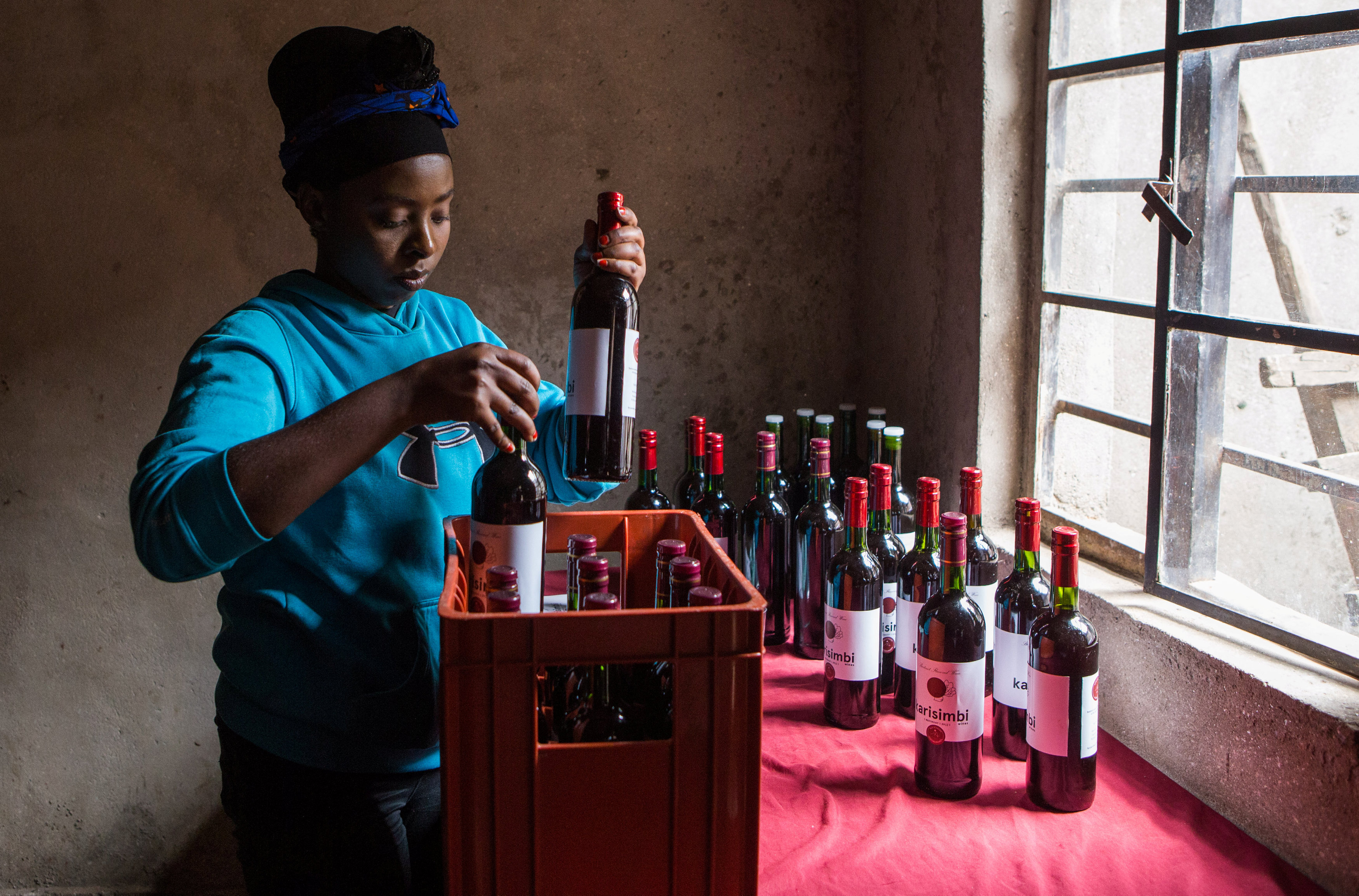 Assoumpata Uwamariya wine bottles from the juice of beetroots at her production stall in Rubavu district, Western province
