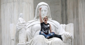 """Protester sits in the lap of """"Lady Justice"""" while demonstrators storm the steps and doors of the U.S. Supreme Court as Judge Kavanaugh is sworn in as a justice inside in Washington"""