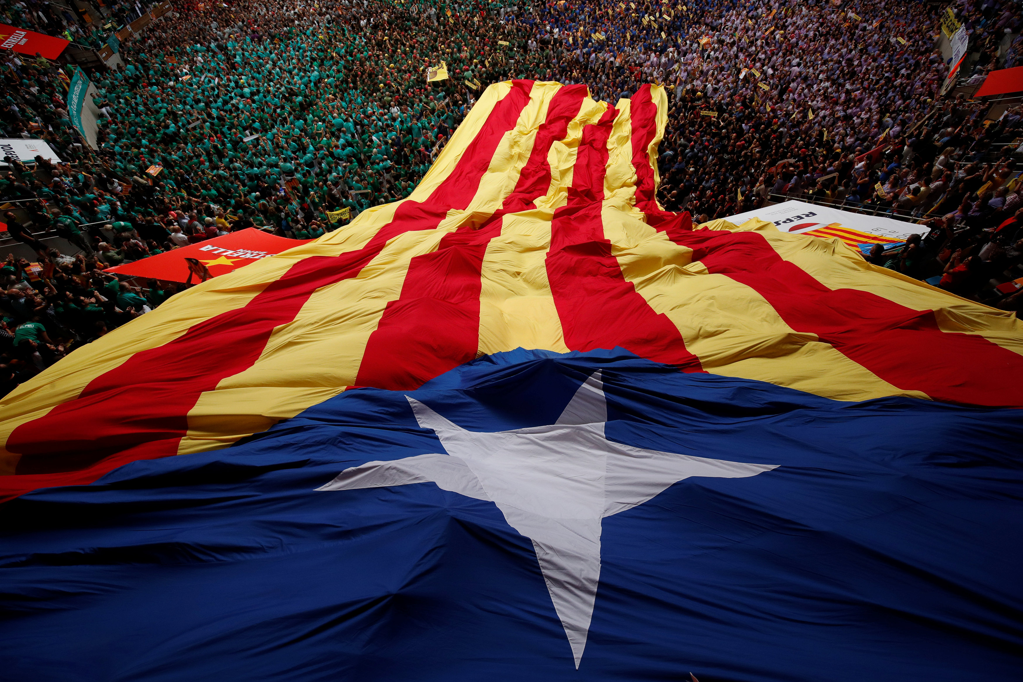 "People unroll gigant ""Estelada"", or Catalan separatist flag, during a biannual competition where people form human towers called ""castell"" in Tarragona"