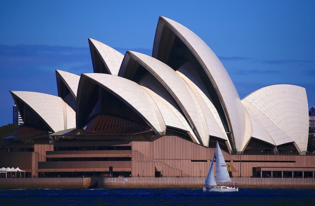 A small yacht sails on Sydney Harbour as it passes the Sydney Opera House in Sydney