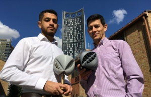 Lancaster University researchers Yaseen Noorani and Nicolas Orellana hold their O-Wind portable turbine prototype, for which they won the UK James Dyson Award, in front of the SE1 Strata building turbine in London