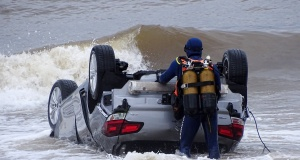 Police divers examine a turned-over car in the sea off Sainte Maxime beach
