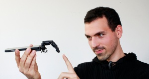 Marc Teyssier, PhD student at Telecom Paris Tech Engineering school, poses with his robot finger 'MobiLimb', that attaches to a mobile phone, after an interview with Reuters in Paris