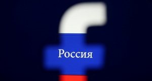 Photo illustration of a 3D printed Facebook logo seen in front of a displayed Russian flag