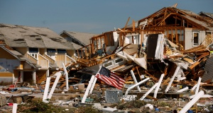 An American flag flies amongst rubble left in the aftermath of Hurricane Michael in Mexico Beach