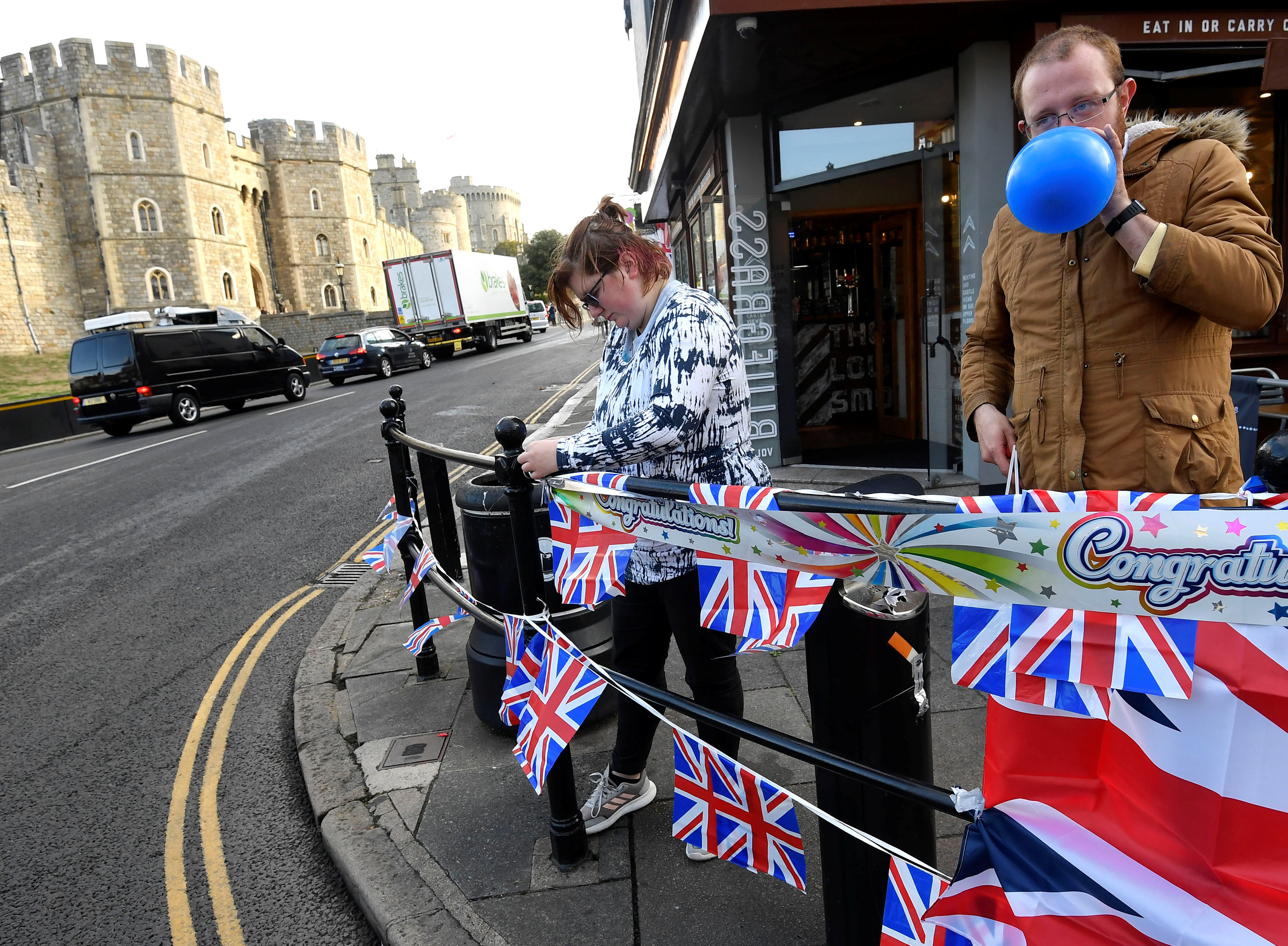 People blow up balloons and string up bunting, on the day before the royal wedding of Britain's Princess Eugenie and Jack Brooksbank, in Windsor
