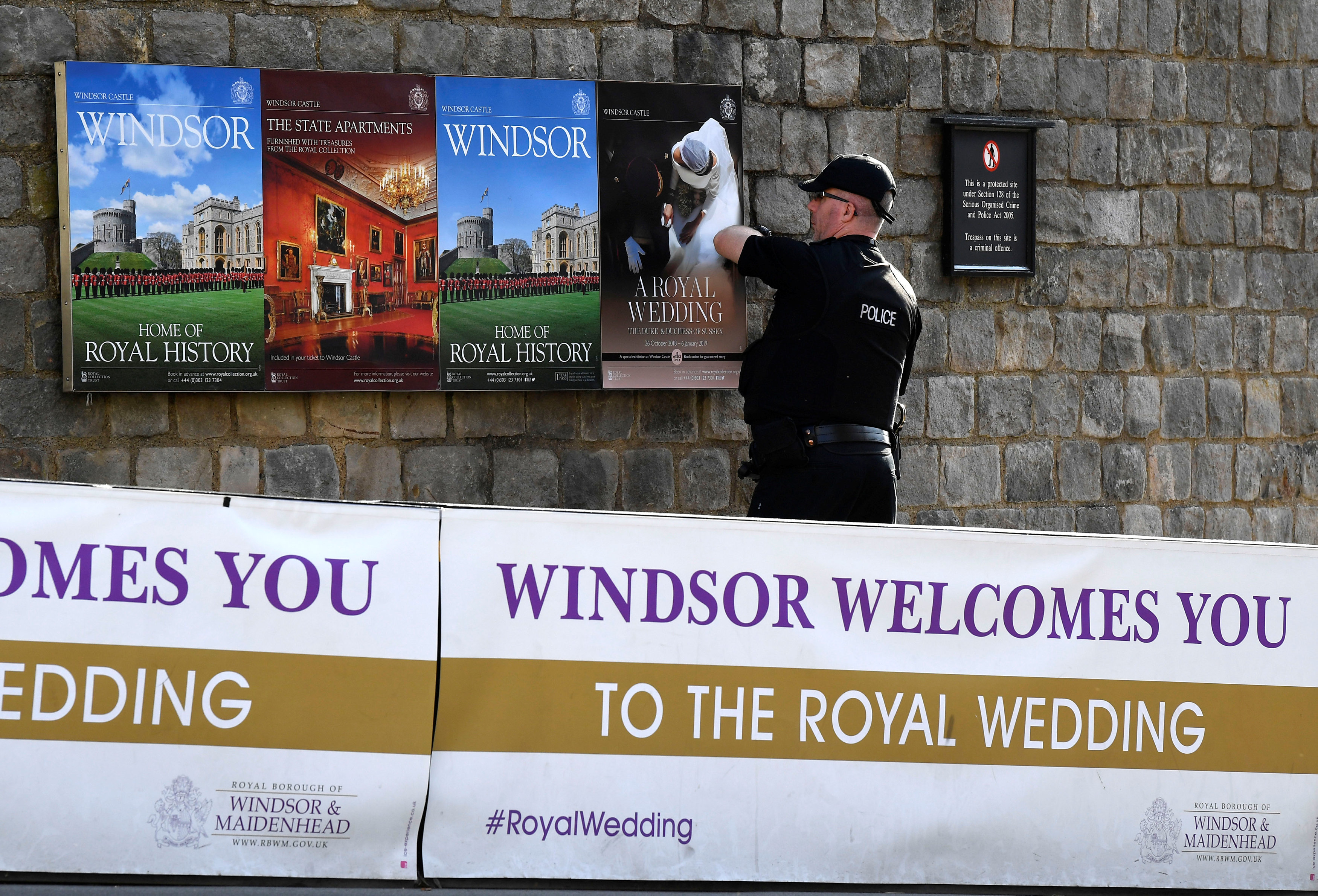 A police officer makes security checks around the castle, on the day before the royal wedding of Britain's Princess Eugenie and Jack Brooksbank, in Windsor