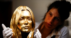 A Sotheby's employee poses with a bust of Kate Moss in solid 18-carat gold during a photocall for 'The Midas Touch' collection at Sotheby's in London