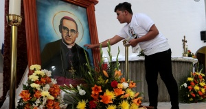 A Catholic young man touches a picture of the late Archbishop of San Salvador Oscar Arnulfo Romero during a mass at the Metropolitan Cathedral in Managua
