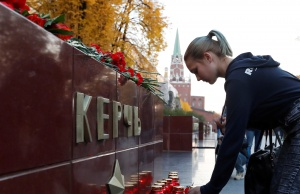 A woman places a candle to commemorate the victims of a fatal attack on a college in the Crimean port city of Kerch, at a memorial by the Kremlin walls in Moscow
