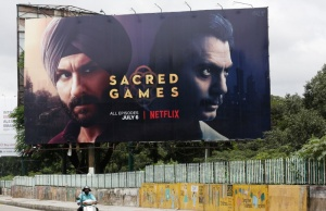 "A man rides his scooter past a hoardings of Netflix's new television series ""Sacred Games"" in Bengaluru,"