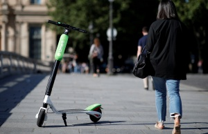 A woman walks past a dock-free electric scooter Lime-S by California-based bicycle sharing service Lime displayed on their launch day in Paris