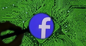 Facebook logo is seen trough magnifier in front of a displayed PC motherboard in this illustration