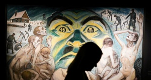 A visitor is silhouetted against a painting during the opening of an exhibition featuring works by David Olere, a prisoner in Auschwitz concentration camp, at the museum in Oswiecim