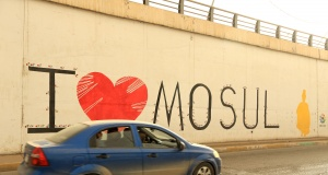 A car drives past a graffiti in the street of Mosul
