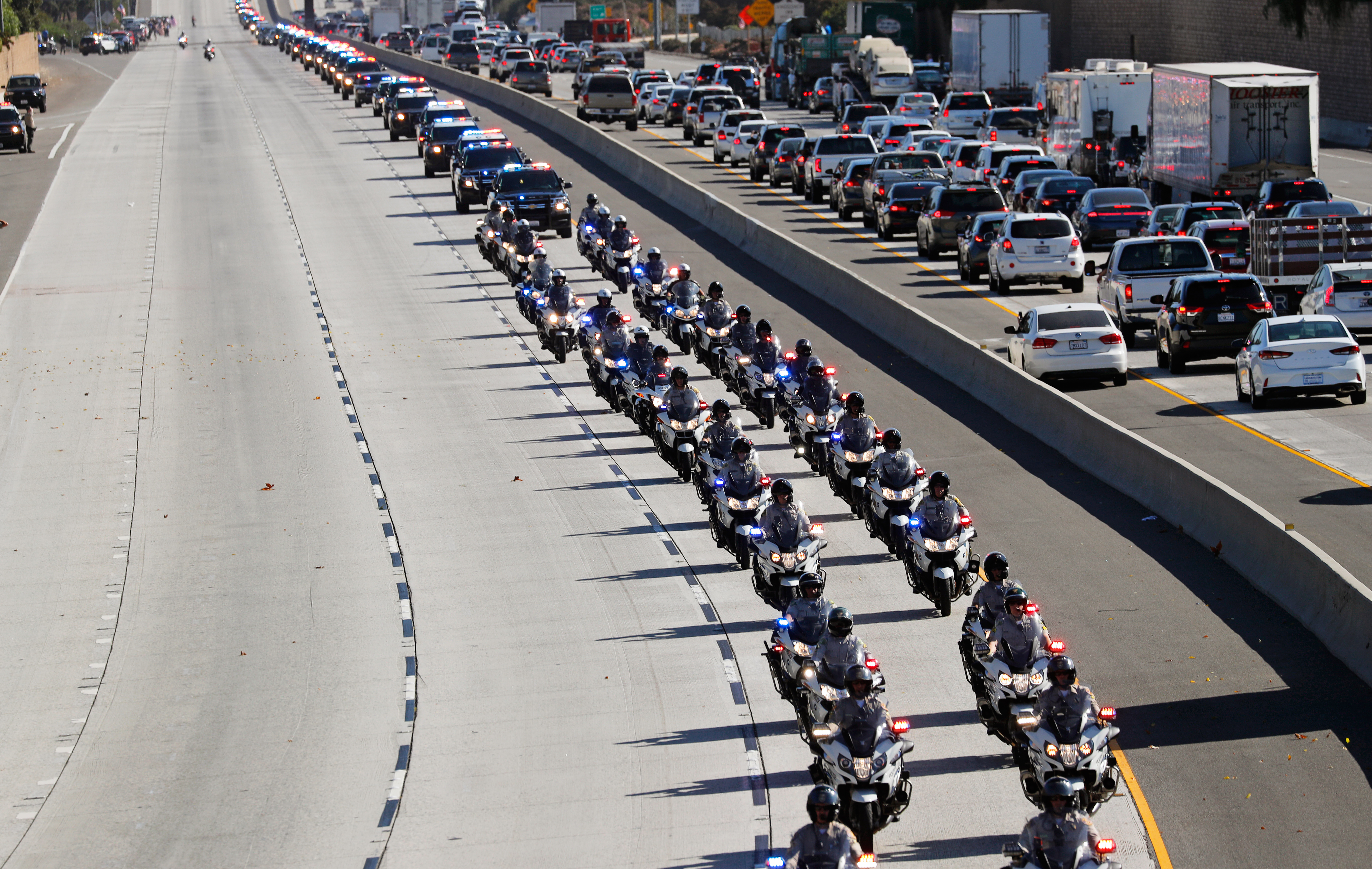 A procession for the body of Sergeant Ron Helus, who died in a shooting incident at a Thousand Oaks bar, drives down Ventura HIghway 101 in Thousand Oaks